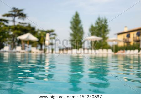 Beautiful house, swimming pool view from the veranda, summer day (Focus on pool water)