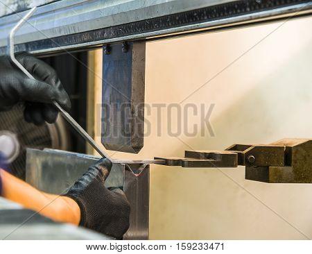 worker operating metal press machine at workshop.