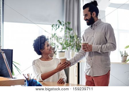 business, startup, people and drinks concept - happy latin man bringing coffee to african woman in office