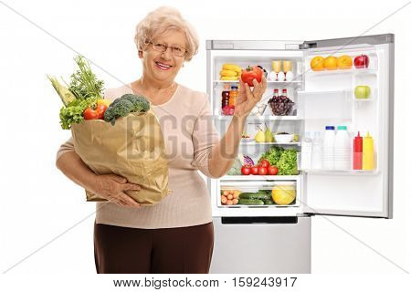 Happy mature woman holding a shopping bag filled with vegetables and a tomato in front of a fridge isolated on white background