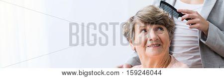 Female carer brushing an older woman's hair