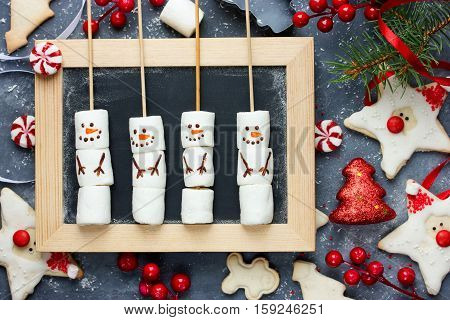 Christmas New Year treats for kids and holiday decorations funny Santa Claus and Christmas tree cookies with icing peppermint candy snowman marshmallow pops. Festive Christmas background