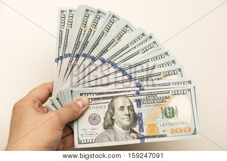 Man's hand holding hundred dollar bank notes