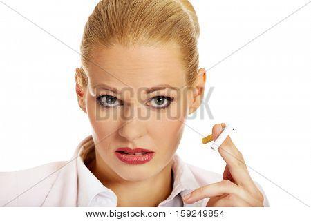 Business woman holding broken cigarette