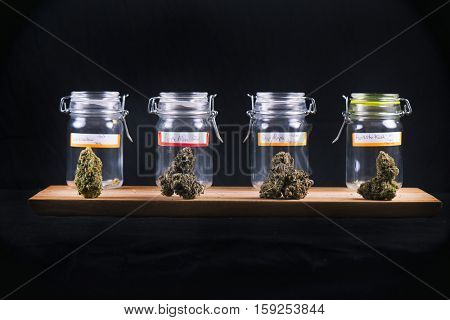 Assorted cannabis bud strains and glass jars isolated on black background - medical marijuana dispensary concept
