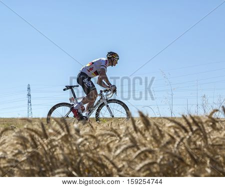 Saint-Quentin-FallavierFrance - July 16 2016: The German cyclist Andre Greipel of Lotto-Soudal Team riding in a wheat plain during the stage 14 of Tour de France 2016.