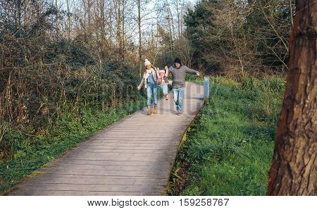 Happy parents holding their daughter by hands to jump over a wooden pathway into the forest