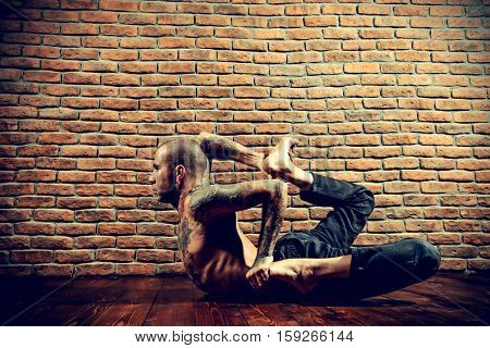 Mature man practicing yoga. Brick wall background. Healthy lifestyle. Meditation, concentration.