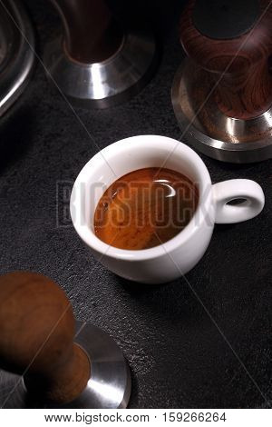 Porcelain white cup of coffee and portafilter of an espresso machine