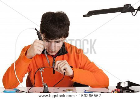 A boy learning to solder wire. Studio shot. Isolated on white background.