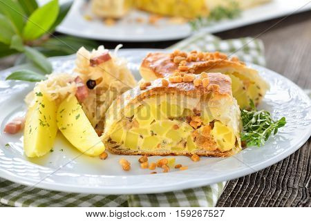 Hearty Austrian cuisine: Potato strudel with greaves, served with bacon sauerkraut