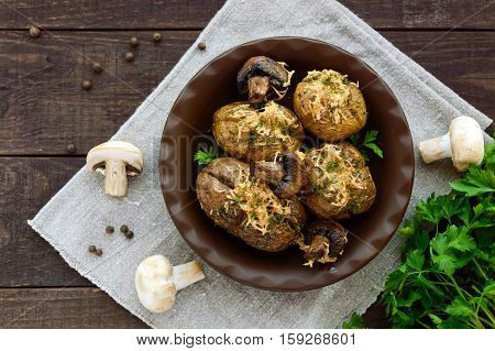 Baked potatoes with mushrooms, cheese and herbs on dark wooden background. The top view