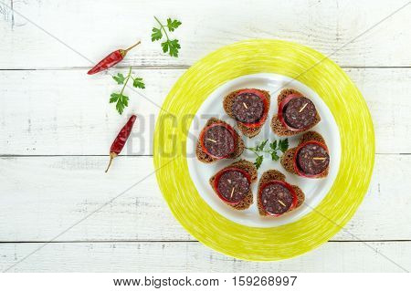 Sandwiches with black rye bread in the shape of a heart blood sausage (Morcillo) and pieces of sweet pepper on skewers on a white wooden background. The top view.