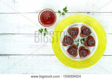 Sandwiches with black rye bread in the shape of a heart blood sausage (Morcillo) and pieces of sweet pepper on skewers and tomato sauce on a white wooden background. The top view.