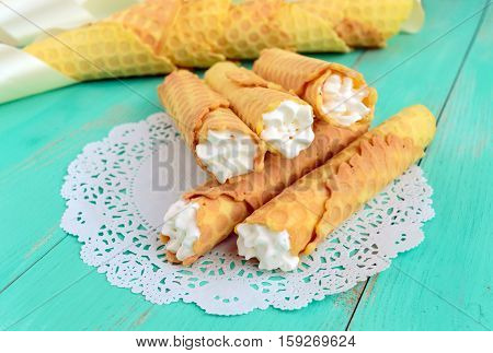 Tender honey wafers in the form of tubes stuffed with air cream on white lace napkin. Close-up.