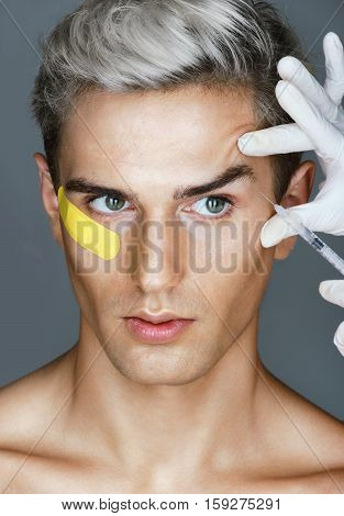 Glamorous man gets beauty injection in eye area from doctor. Cosmetology. Beauty Beauty concept
