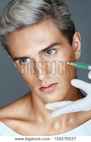 Beautiful young man gets beauty injection in eye area from doctor. Cosmetology. Beauty concept