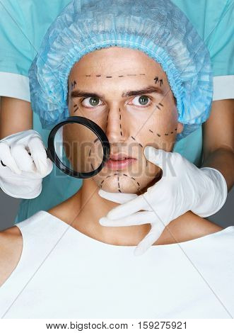 Nurse with magnifying glass near the face of the patient. Surgical mark lines on eyes nose cheek and jaw