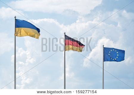 Flags of Ukraine Germany and the European Union flutter on wind in sunny day against the background of cumulus clouds.