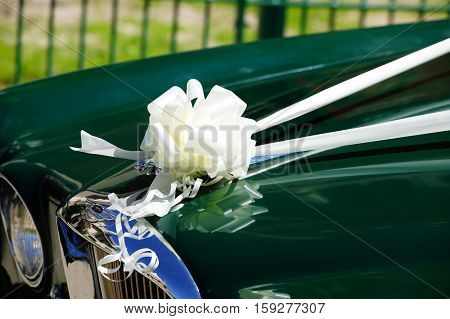 London, UK, May 23, 2010 : Wedding car with its white silk band and bow celebrating a white wedding outside a church waiting for the bride and groom