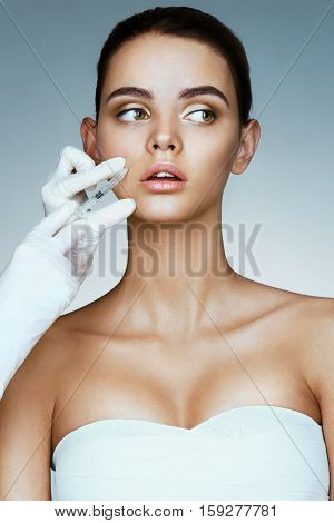 Beautiful woman face and beautician hands with syringe. Professional cosmetician making rejuvenate injection. Clean Beauty concept