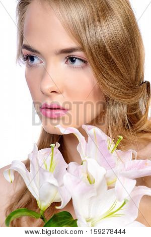 Sensual young woman with natural make-up holding white lily. Beauty, fashion, cosmetics. Spa, body care. Isolated over white.