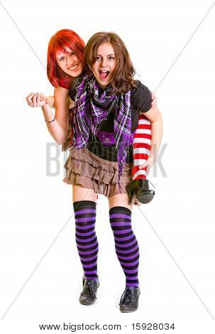 Two happy girlfriends funny posing together isolated on white