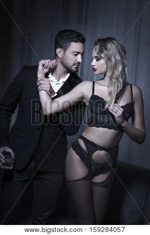 Sexy macho man holding blonde lovers arm sensuality