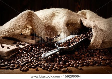 Fresh coffee beans with sack and scoop, closeup