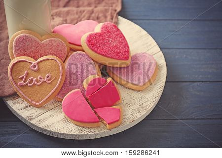 Heart shaped cookies with milk on wooden table, closeup