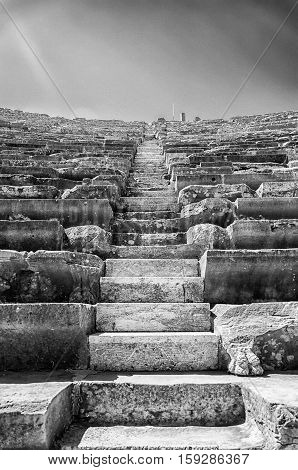 A black and white image of the ancient Roman amphitheatre situated in the turkish town of Side with added noise and contrast for dramatic effect.