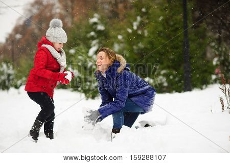Young beautiful woman and her daughter builds snowman. Woman and girl are dressed in bright and warm jackets. It is snowing. Mother without headdress. Snowflakes fall her on the face.