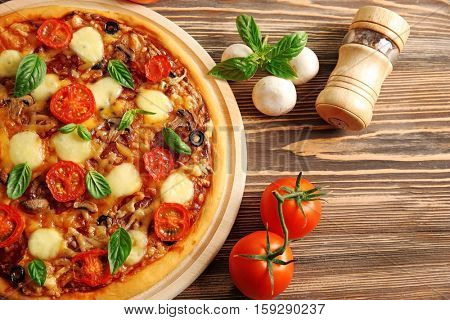 Fresh pizza with tomatoes, cheese and mushrooms on wooden background