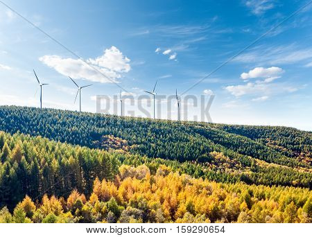 wind turbines on the hillside with forest in autumn