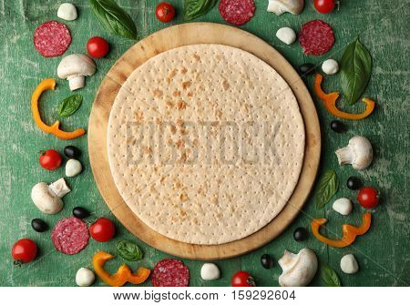 Raw pizza ingredients on wooden background, top view