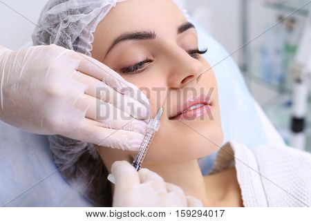 Beautiful girl on rejuvenation procedure in beauty clinic filler injection.