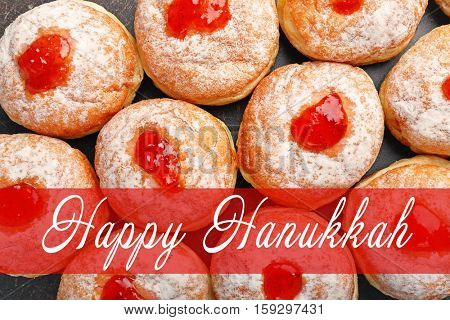 Tasty donuts, closeup. Hanukkah celebration concept. Text HAPPY HANUKKAH