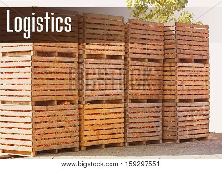 Wooden crates with harvest, outdoor. Word LOGISTICS on background. Wholesale and logistics concept.