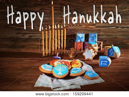 Traditional composition for Hanukkah on wooden background. Hanukkah celebration concept. Text HAPPY HANUKKAH