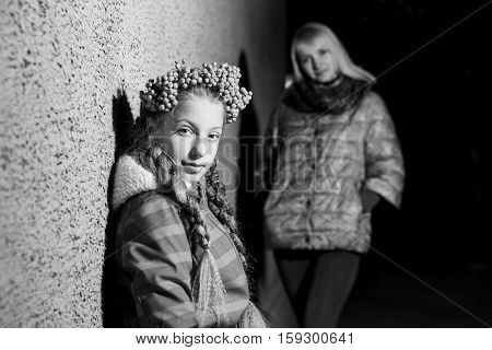 mother and daughter with a wreath of rowan stand near the walls evening