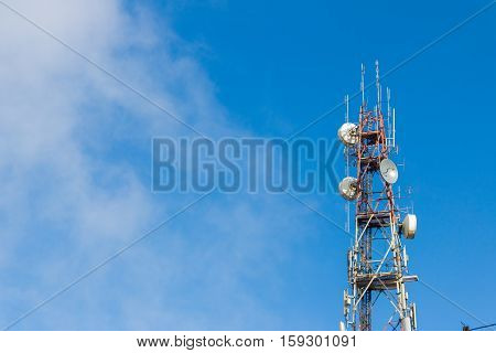 telecommunication tower antenna with blue sky and cloud background.