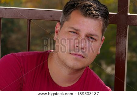 Young man on a balcony relaxing on a autumn sunny day