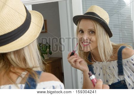 beautiful smiling blond woman with mirror putting lip-gloss