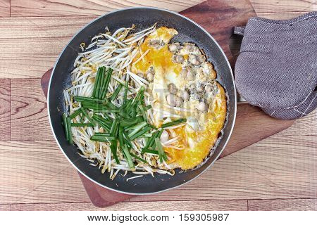 Ready fried oyster omelet with bean sprouts and shallot call Hoi Tod Khai in Thai served in pan
