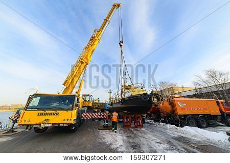 MOSCOW, RUSSIA - NOVEMBER 11, 2016: State Unitary Enterprise Mosvodostok performs recovery vessels on coastal winter parking. Truck Crane sets the ship to the shore.