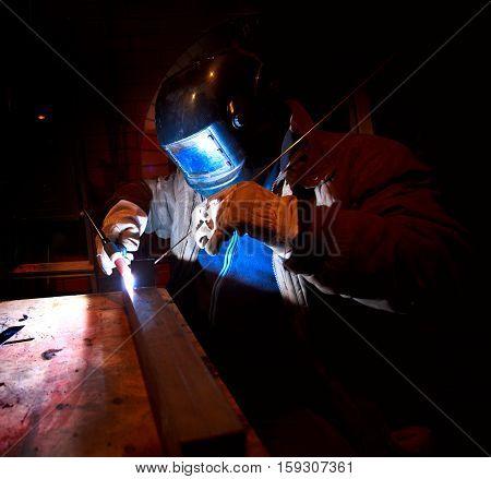 worker welding construction by welding man mask