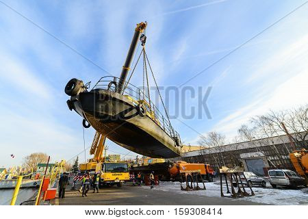 MOSCOW, RUSSIA - NOVEMBER 11, 2016: State Unitary Enterprise Mosvodostok performs recovery vessels on coastal winter parking. Truck crane carries the ship to the shore.