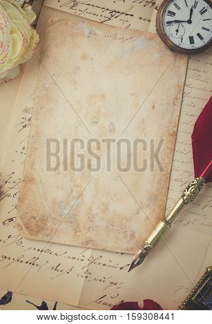old blank paper on pile of old letters with feather pen, retro toned