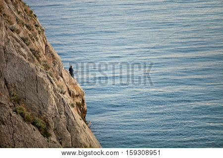 On a rock in the sea is a man and a fisherman is fishing on the fishing rod. The Rock is in the sea. Seascape on a sunny day. Sunset. On the rock plants grow. On the sea is calm. Extreme hobby.