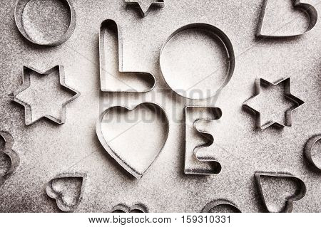 Cookie cutters shaped in Love with flour lying on black background. Baking cookies concept.